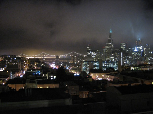 Downtown San Francisco illuminates the foggy night sky