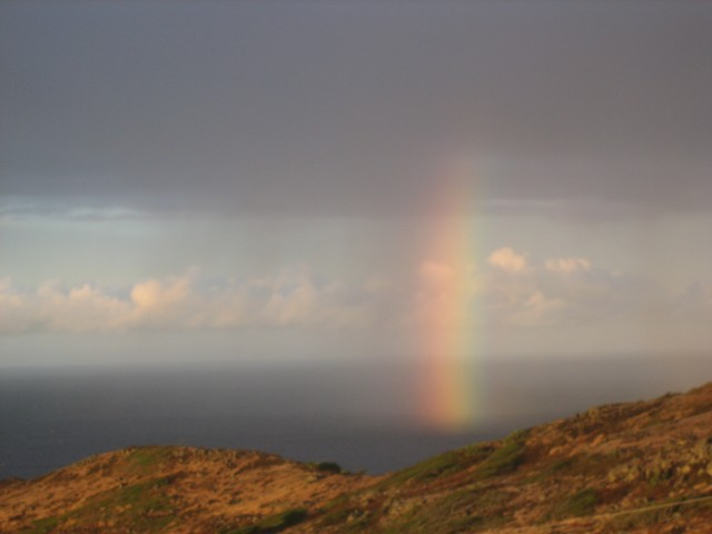 At the end of our sunrise hike, a rainbow dips into the Pacific Ocean off the coast of Hawaii